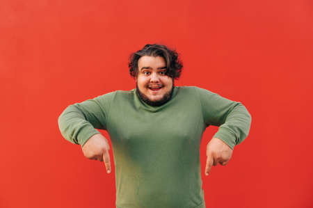 Cheerful and funny young bearded fat guy is standing on a red background and pointing his fingers down, indicating on a copy space, advertising.