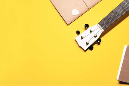 Colorful flat lay photo on an isolated yellow background with a wooden hawaiian ukulele guitar fretboard, two brown notepads, and a guitar pick. Archivio Fotografico