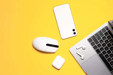 Conceptual flat lay with mostly white devices: computer mouse, mobile phone, wireless earphones; and a silver gray laptop on an isolated yellow background.