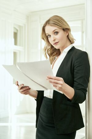 A blonde businesswoman is reading. She is holding papers in her hands. Office, home office.