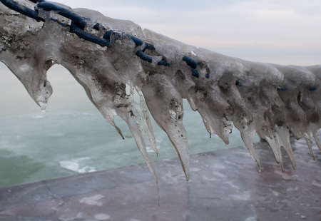 landing stage: Icicles on a chain of a landing stage Stock Photo