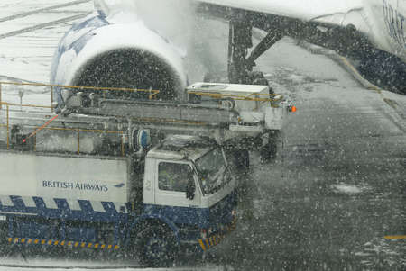 LONDON - JANUARY 18, 2013: Deicing of an aircraft in the snowstorm at Heathrow airport on January 18, 2013 in London.Thousands of travelers stuck at Heathrow airport due to the heavy snowing.
