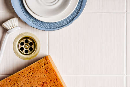 Ceramic dishes in the sink with a brush and sponge