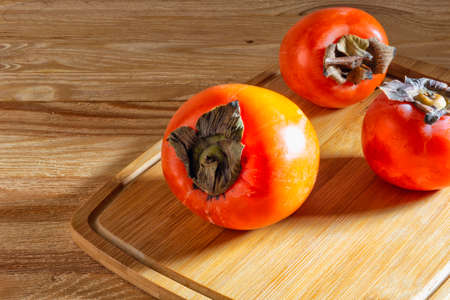 Sweet and juicy persimmon fruits are on the table