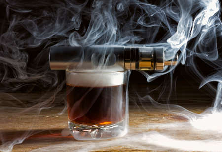 Electronic cigarette lying on a glass of whiskey in a cloud of vapor