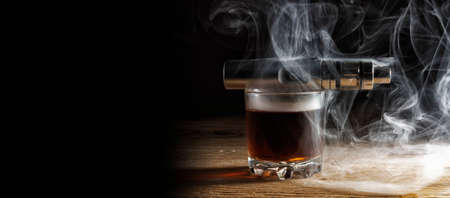 Electronic cigarette lying on a glass of whiskey shrouded in steam