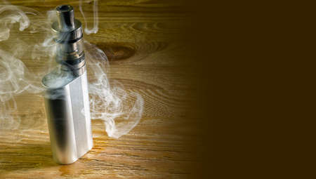 Electronic cigarette standing on the table shrouded in steam