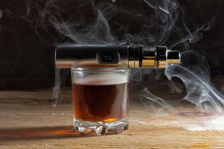 Electronic cigarette on a glass of whiskey shrouded in steam