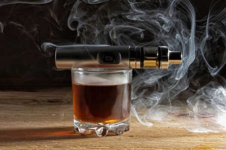 Electronic cigarette on a glass of whiskey in a cloud of vapor