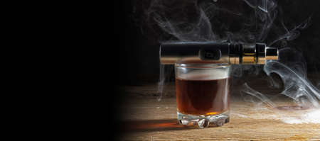 Electronic cigarette lying on a glass of whiskey in a steam enveloped