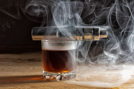 Electronic cigarette lying on a glass of brandy shrouded in steam 版權商用圖片