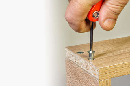 Screwing with a tool, a threaded furniture fastener 版權商用圖片