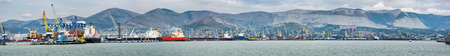 Industrial port, at the foot of the mountains, panorama