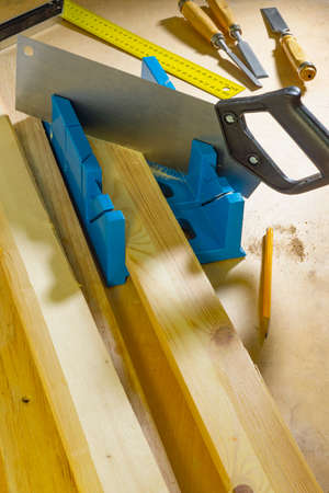 Sawing parts at an angle using a miter box and a hacksaw. 版權商用圖片