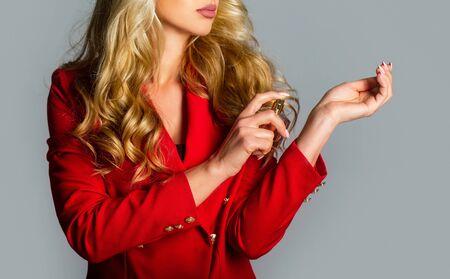 Beautiful girl using perfume. Woman with bottle of perfume. Perfume bottle woman spray aroma. Woman holding a perfumes bottle. Woman presents perfumes fragrance. Woman with perfum bottle.