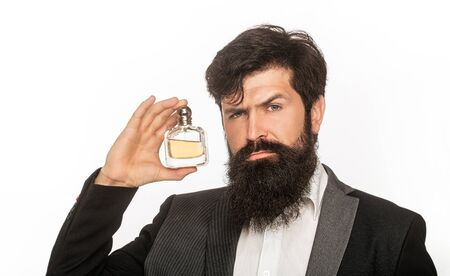 Perfume or cologne bottle, perfumery, cosmetics, scent cologne bottle, male holding cologne. Masculine perfume, bearded man in a suit. Male holding up bottle of perfume. Closeup portrait