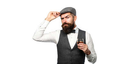 Stylish rich man holding a glass of old whisky. Bearded gentleman drink cognac. Sipping finest whiskey. Portrait of man with thick beard. Macho drinking