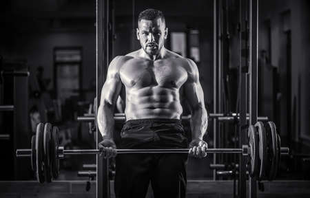 Bodybuilder athletic man with six pack, perfect abs, shoulders, biceps, triceps, chest. Barbells workout. Muscular man workout with barbell at gym. Black and white