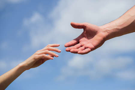 Hands of man and woman reaching to each other, support. Giving a helping hand. Hands of man and woman on blue sky background. Lending a helping hand. Solidarity, compassion, and charity, rescue