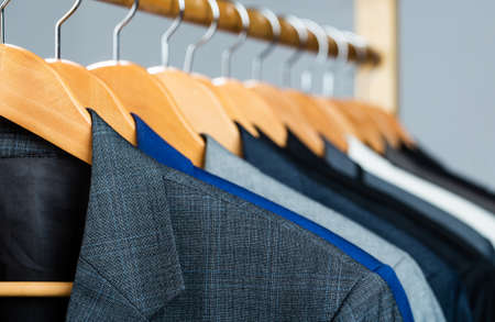Suits for men hanging on the rack. Mens suits in different colors hanging on hanger in a retail clothes store, close-up. Mens shirts, suit hanging on rack. Hangers with jackets on them in boutique