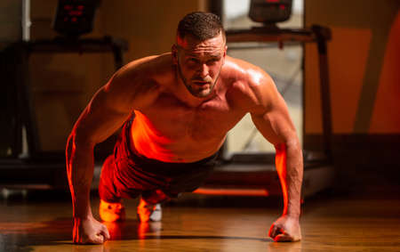 Man doing push-ups. Muscular and strong guy exercising. Slim man doing some push ups a the gym. Muscular man doing push-ups on one hand against gym background. Sport
