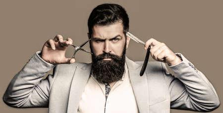 Bearded client visiting barber shop. Barber scissors and straight razor, barber shop, suit. Brutal guy, scissors, straight razor