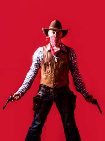 American bandit in mask, western man with hat. Man wearing cowboy hat, gun. West, guns. Portrait of a cowboy. owboy with weapon on red background 免版税图像