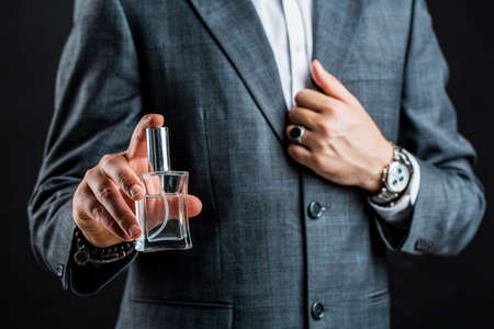 Male holding up bottle perfume. Hand in with wrist watch in a business suit. Perfume or cologne bottle and perfumery, cosmetics, scent cologne bottle, male holding cologne