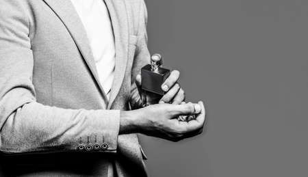 Man holding up bottle of perfume. Men perfume in the hand on suit background. Man in formal suit, bottle of perfume, closeup. Fragrance smell. Fashion cologne bottle. Copy space. Copy space