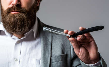 Straight razor, barbershop, beard. Vintage straight razor. Mens haircut. Man in barbershop. Handsome bearded hairdresser is holding a straight razor while barbershop