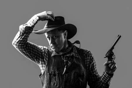 Portrait of a cowboy. American bandit in mask, western man with hat. Portrait of farmer or cowboy in hat. Portrait of a cowboy. West, guns. Black and white