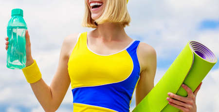 Smiling happy fitness girl with yoga mat over sky background. Woman in sports wear is holding a yoga mat and a bottle of water and smiling. Healthy lifestyle concept