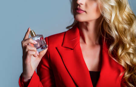 Woman holding a perfumes bottle. Woman presents perfumes fragrance. Woman with perfum bottle Standard-Bild