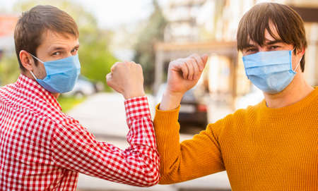 Coronavirus, illness, infection, quarantine, medical mask. Friends medical mask. Elbows bump. Friends in protective medical mask on his face greet their elbows in a quarantine