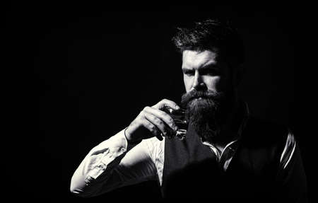 Bearded drink cognac. Sommelier tastes drink. Man holding a glass of whisky. Closeup portrait. Sipping whiskey. Portrait of man with thick beard. Macho drinking. Man with beard holds glass brandy
