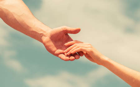 Hands of man and woman on blue sky background. Lending a helping hand. Solidarity, compassion, and charity, rescue Archivio Fotografico