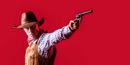 West, guns. Portrait of a cowboy. American bandit in mask, western man with hat. Portrait of cowboy in hat. Portrait of man wearing cowboy hat, gun. Portrait of a cowboy