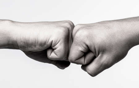 People bumping their fists together, arms. Man giving fist bump. Team concept. Hands of man people fist bump team teamwork, success. Friendly handshake, friends greeting. Black and white Imagens