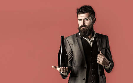 Man holding bottle with champagne, wine. Bearded man with a bottle champagne of and glass. Stylish male in tuxedo. Space for text. The person holds a red wine bottle in a hand. Copy space