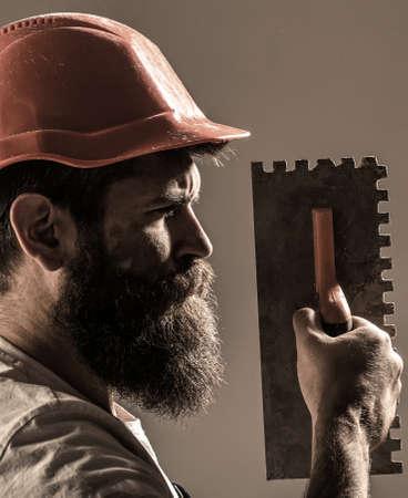 Mason plastering concrete to build. Plastering tools. Tool, trowel, handyman, man builder. Mason tools, builder. Builders in hard hat, helmet. Bearded man worker, beard, building helmet Stockfoto