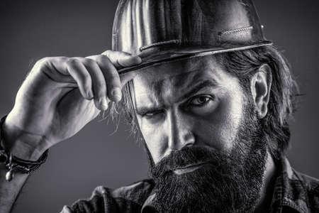 Man builders, industry. Builder in hard hat, foreman or repairman in the helmet. Building, industry, technology - builder concept. Black and white Foto de archivo