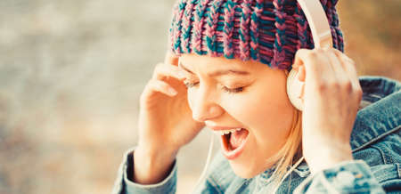 Outdoors portrait of a trendy girl. Girl listens to music in headphones. Smiling girl relaxing, music a smartphone and headphones