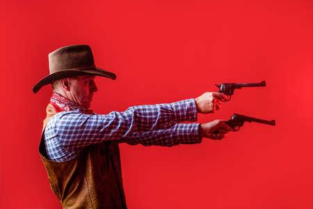 Man wearing cowboy hat, gun. Portrait of a cowboy. West, guns. Portrait of a cowboy. Western man with hat. Portrait of farmer or cowboy in hat. American farmer