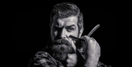 Handsome bearded hairdresser is holding a straight razor while barbershop. Straight razor, barbershop, beard. Black and white