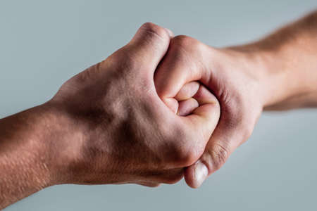 Friendly handshake, friends greeting. Rescue, helping hand. Male hand united in handshake. Man help hands, guardianship, protection Foto de archivo