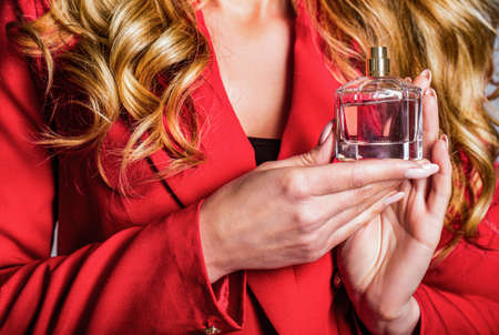 Womans with perfum bottle. Beautiful girl using perfume. Woman with bottle of perfume. Perfume bottle woman spray aroma. Woman holding a perfumes bottle. Woman presents perfumes fragrance