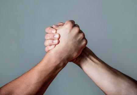 Man hand. Two men arm wrestling. Arms wrestling. Closep up. Friendly handshake, friends greeting, teamwork, friendship. Handshake, arms, friendship. Hand, rivalry, vs, challenge, strength comparison Zdjęcie Seryjne
