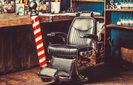 Barber shop pole. Logo of the barbershop, symbol. Stylish vintage barber chair. Hairstylist in barbershop interior. Barber shop chair. Barbershop armchair, barber shop for men