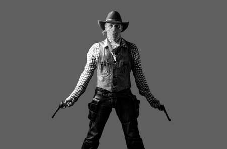 Man wearing cowboy hat, gun. West, guns. American bandit in mask, western man with hat. Portrait of farmer or cowboy in hat. Cowboy with weapon on background. Black and white