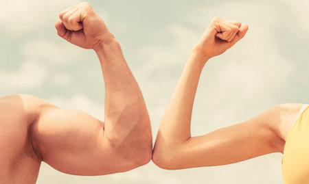 Muscular arm vs weak hand. Vs, fight hard. Competition, strength comparison. Rivalry concept. Hand, man arm fist Close-up. Rivalry, vs, challenge, strength comparison. Sporty man and woman Archivio Fotografico